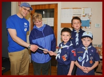 Cub Scouts from Pack 77 present a check to Board Members Craig Bonaceto and Merri Serra